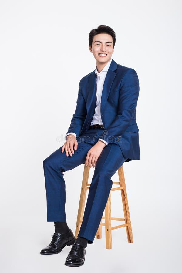 Portrait de studio d'un jeune homme asiatique d'affaires s'asseyant dans une chaise photo stock