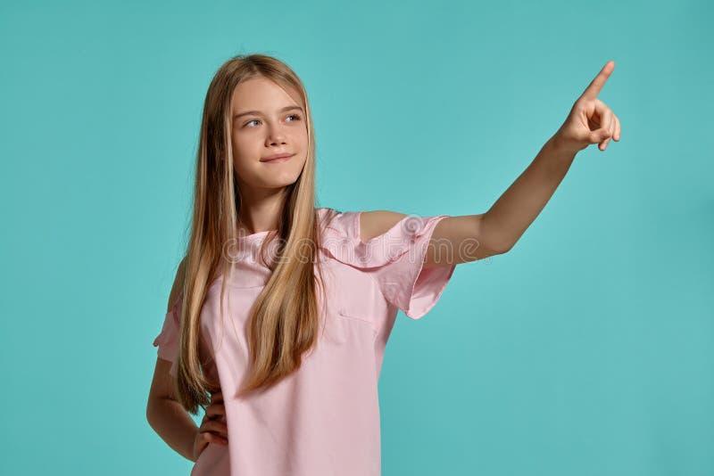 Portrait de studio d'une adolescente blonde de belle fille dans un T-shirt rose posant au-dessus d'un fond bleu photographie stock