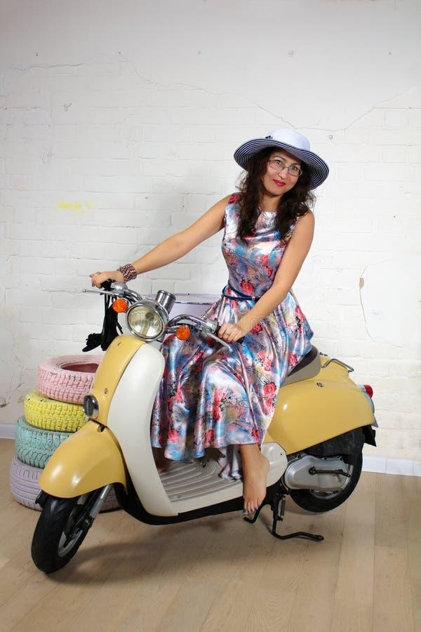 Portrait de studio d'une jeune femme asiatique heureuse sur le scooter photos stock