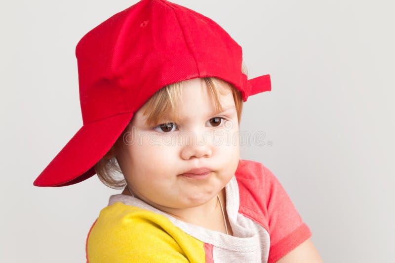 Portrait de studio de fille confuse drôle dans la casquette de baseball rouge photos stock