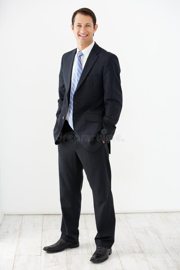Portrait de studio de fond de Standing Against White d'homme d'affaires images stock