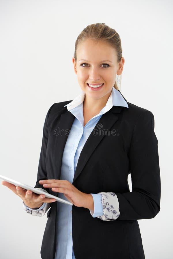 Portrait de studio de fond de Standing Against White de femme d'affaires utilisant la Tablette de Digital photographie stock