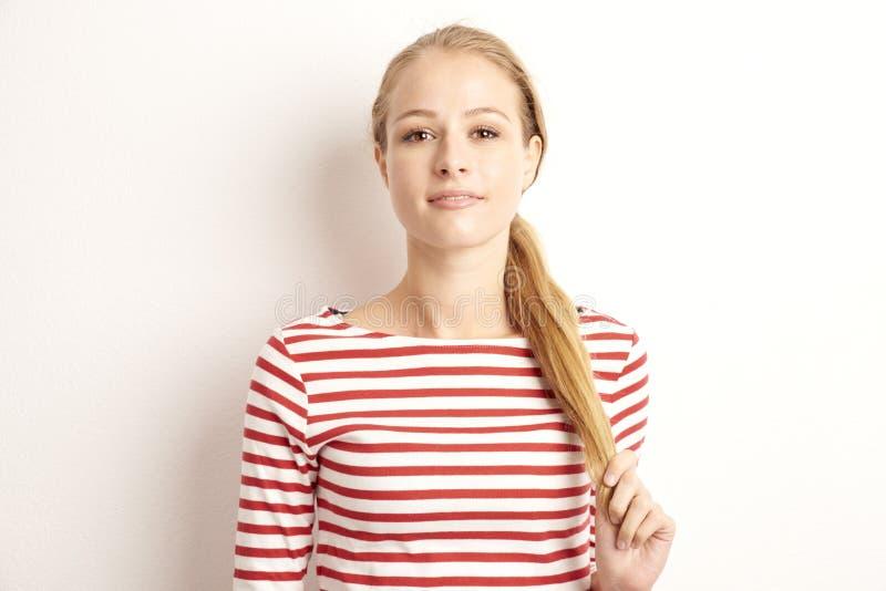 Portrait de studio de joli lookig de jeune femme à la caméra et au sourire tout en se tenant au fond blanc d'isolement et jouant  image stock