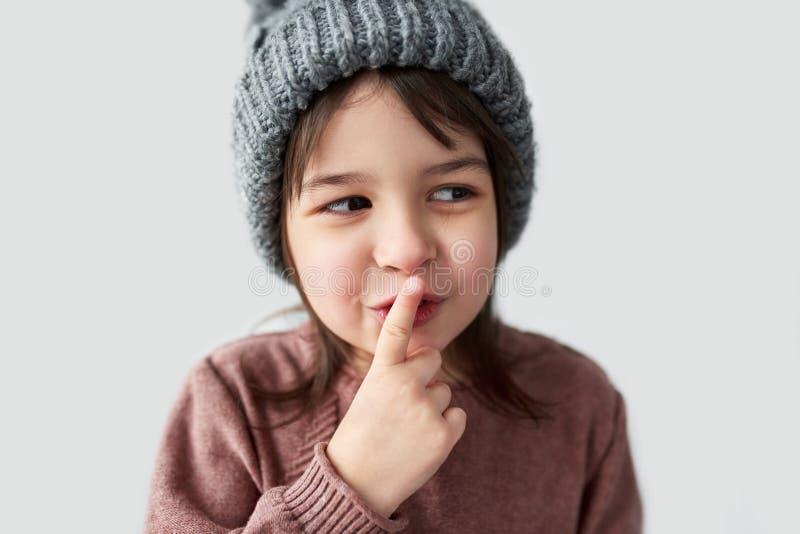 Portrait de studio de plan rapproché de belle petite fille heureuse dans le chapeau gris chaud d'hiver, le chandail de port et la images libres de droits