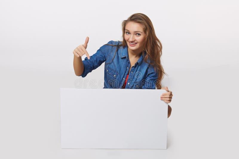 Portrait de style de denim de fille de l'adolescence sur le plancher tenant le bla blanc photos stock