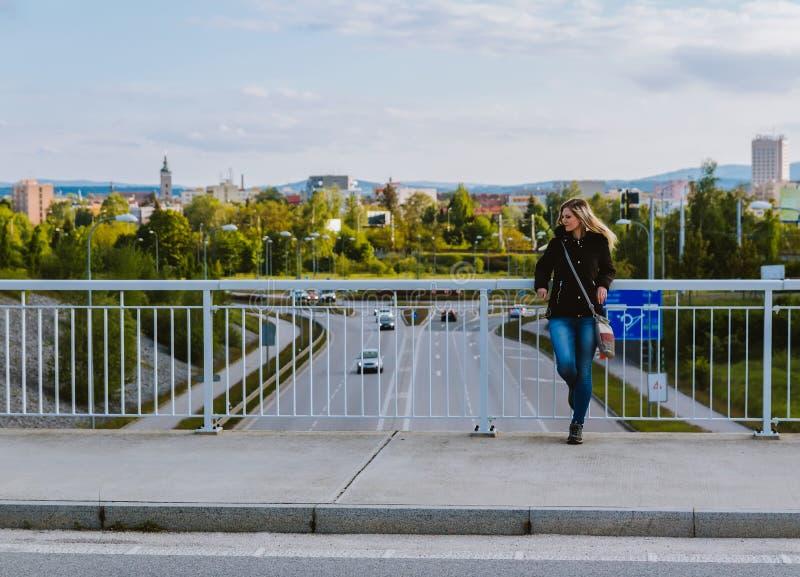Portrait de support blond de jeune femme de beauté sur le pont dans la veste avec la ville Ceske Budejovice dans le bacground photographie stock