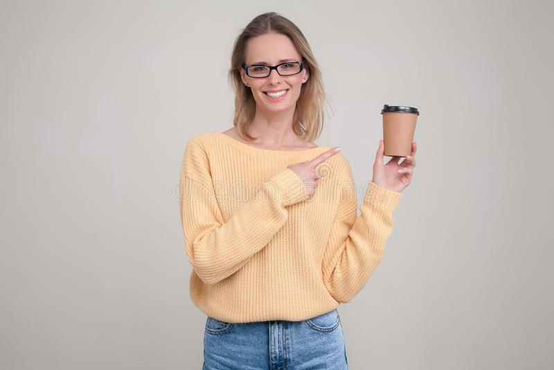 Portrait de taille- de femme blonde tenant le chapeau de caf? dans des ses mains et souriant, regardant la cam?ra, se dirigeant a photo libre de droits
