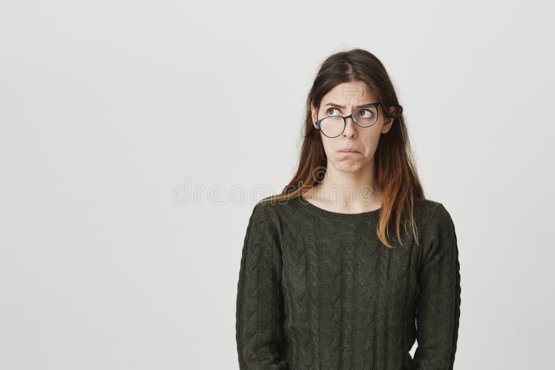 Portrait de taille- de modèle femelle caucasien de pensée mécontent avec de longs cheveux bruns, regardant loin avec les verres d images stock