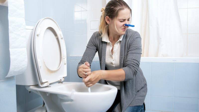 Portrait de toilette exigeante de nettoyage de jeune femme avec la brosse photo libre de droits