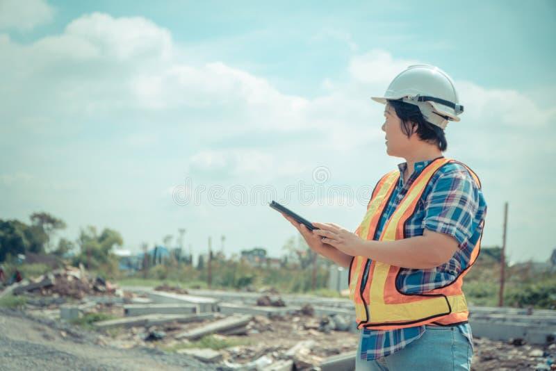 Portrait de travailleur asiatique d'ingénieur de construction de femme avec le casque sur la tête utilisant le comprimé tout en s photographie stock libre de droits