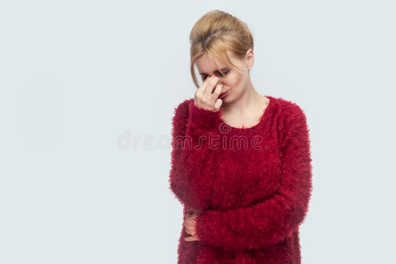 Portrait de triste seulement ou belle jeune femme blonde fatiguée dans la position rouge de chemisier, maintenant la tête et pleu images libres de droits