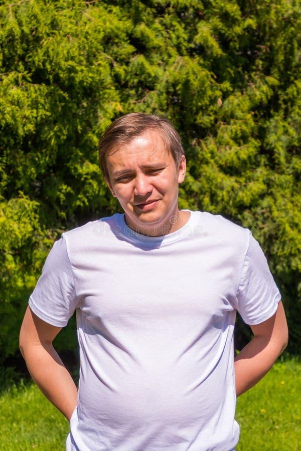 Portrait de triste un homme dans une position blanche de T-shirt ext?rieure en parc photo stock