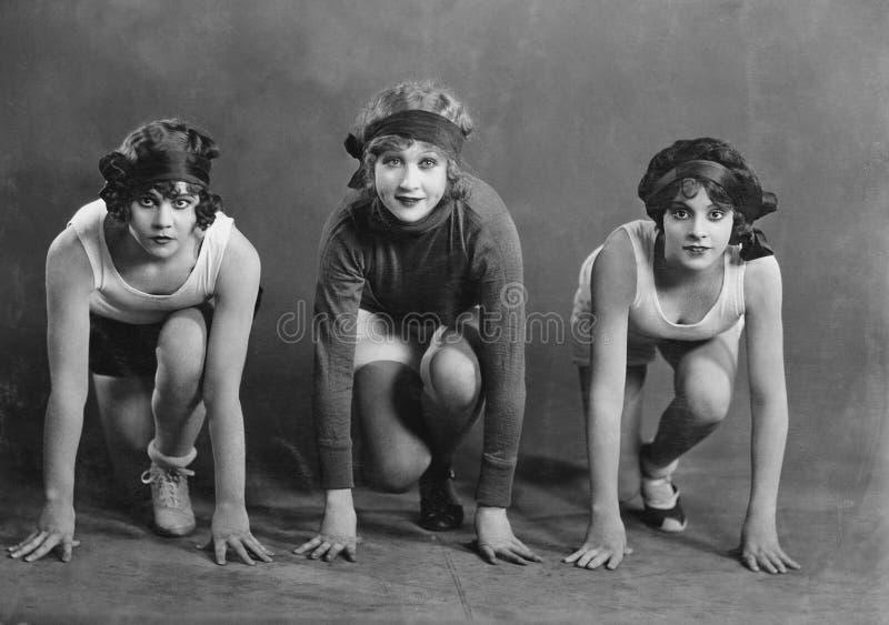 Portrait de trois coureurs femelles en position de départ (toutes les personnes représentées ne sont pas plus long vivantes et au photos libres de droits