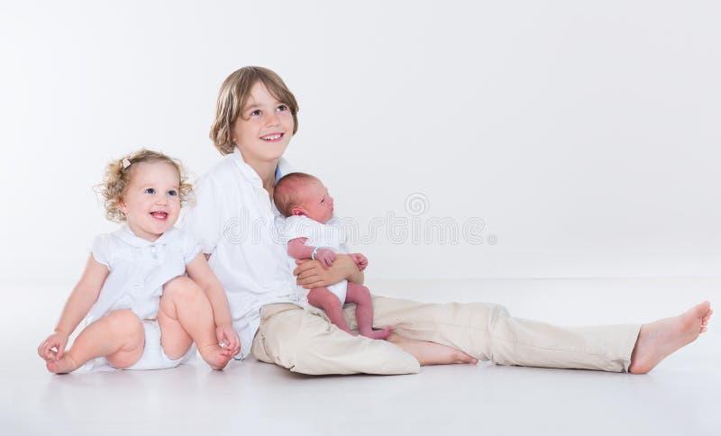 Portrait de trois enfants de mêmes parents avec les vêtements blancs photos libres de droits