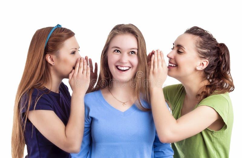 Portrait de trois femelles caucasiennes heureuses partageant des secrets et le RU image libre de droits