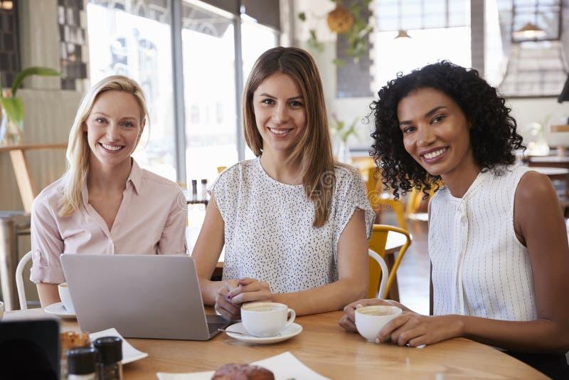 Portrait de trois femmes d'affaires se réunissant dans le café images stock