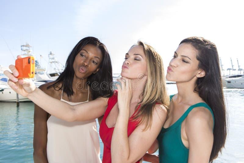 Portrait de trois femmes prenant des selfies de canard-visage avec un smartphone photo libre de droits