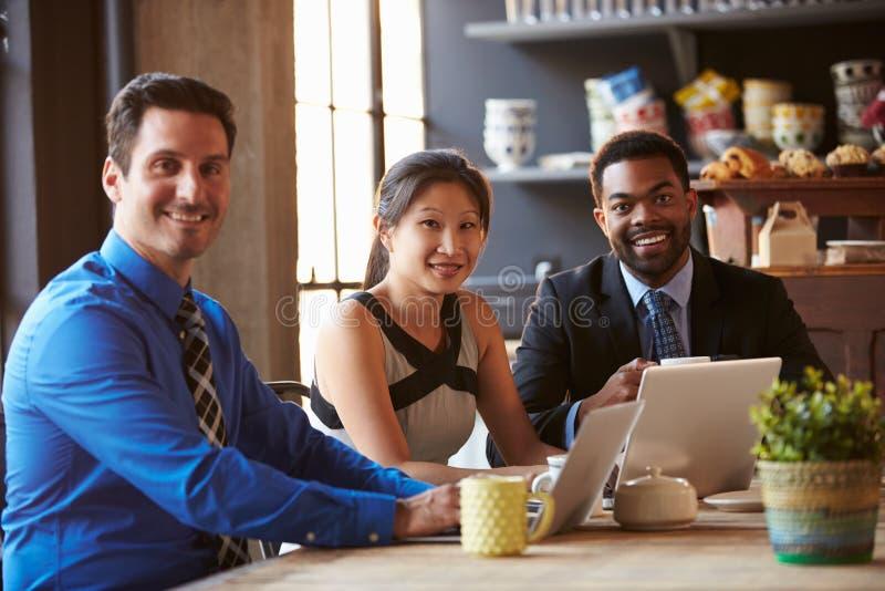 Portrait de trois hommes d'affaires travaillant à l'ordinateur portable en café image stock