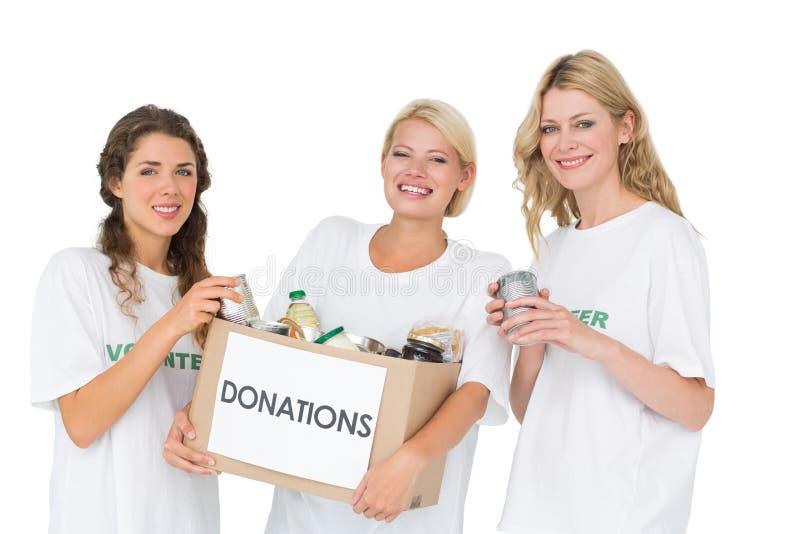 Portrait de trois jeunes femmes de sourire avec la boîte de donation photographie stock