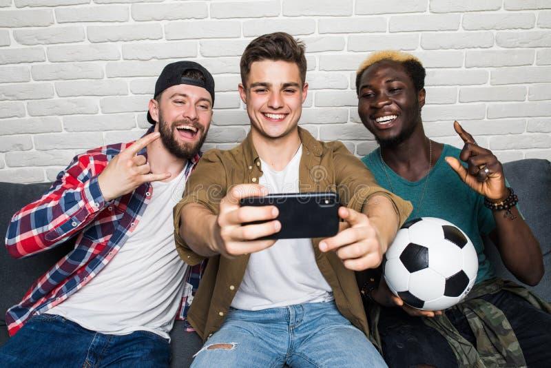 Portrait de trois jeunes hommes heureux prenant un selfie tout en se reposant à la maison avec de la bière et des casse-croûte su images stock