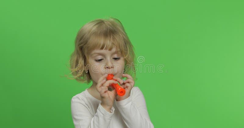 Portrait de trois jeux blonds de fille d'années sur le tuyau de jouet sur le fond vert photo stock