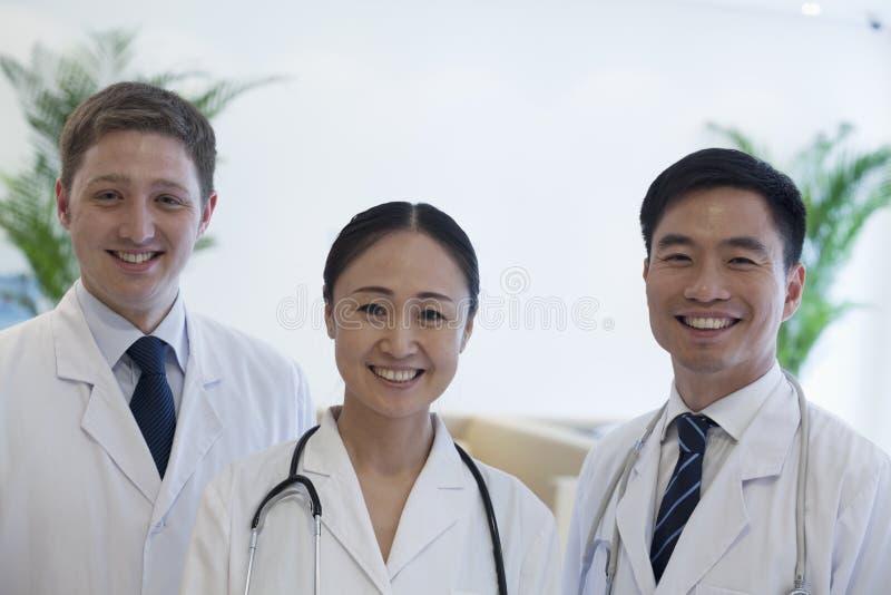Portrait de trois médecins de sourire dans l'hôpital, groupe multi-ethnique images libres de droits