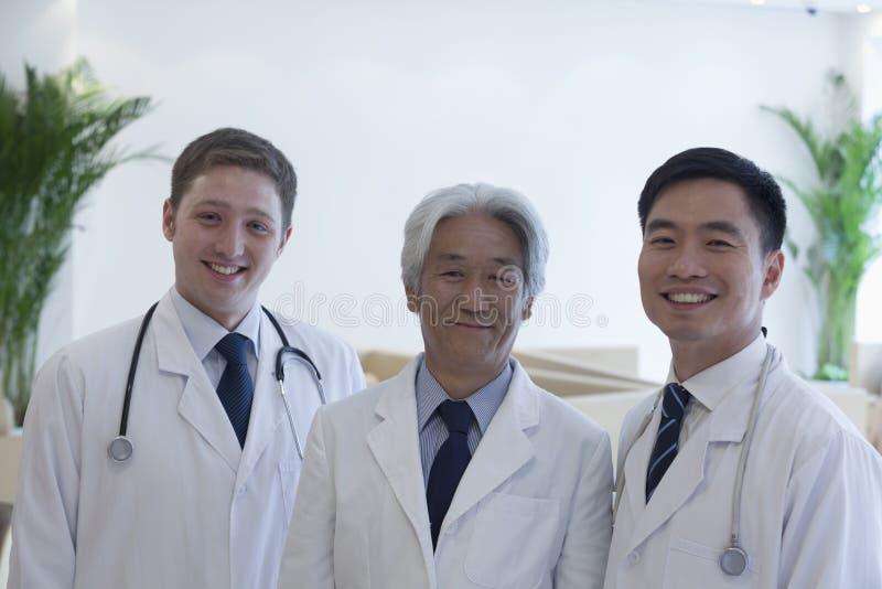 Portrait de trois médecins de sourire dans l'hôpital, groupe multi-ethnique photos stock