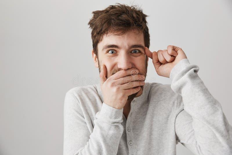 Portrait de type adulte étrange fou avec les cheveux malpropres, couvrant la bouche de paume et tournant l'index au-dessus du tem images libres de droits