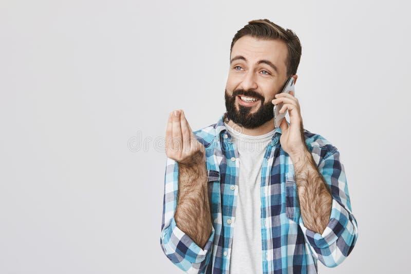 Portrait de type attirant riant, parlant par l'intermédiaire du smartphone au sujet de quelque chose hilare, montrant le geste it photo libre de droits