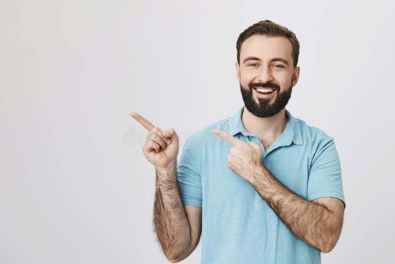 Portrait de type barbu beau gai avec le sourire brillant dans le T-shirt bleu, se dirigeant à gauche avec les deux index photographie stock libre de droits