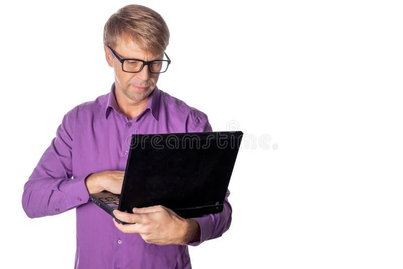 Portrait de type beau en chemise et verres occasionnels utilisant l'ordinateur portable Fonctionnement d'homme occupé photo stock