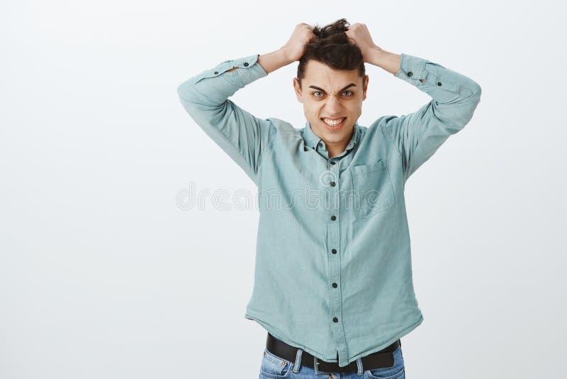 Portrait de type beau outragé agressif, retirant des cheveux de colère et regardant de dessous le front avec la grimace photos stock