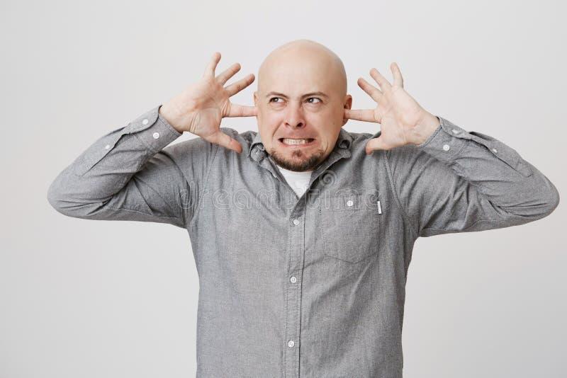 Portrait de type contrarié et fâché avec la barbe fermant ses oreilles avec des doigts au-dessus du fond blanc Homme dans une mau photos libres de droits