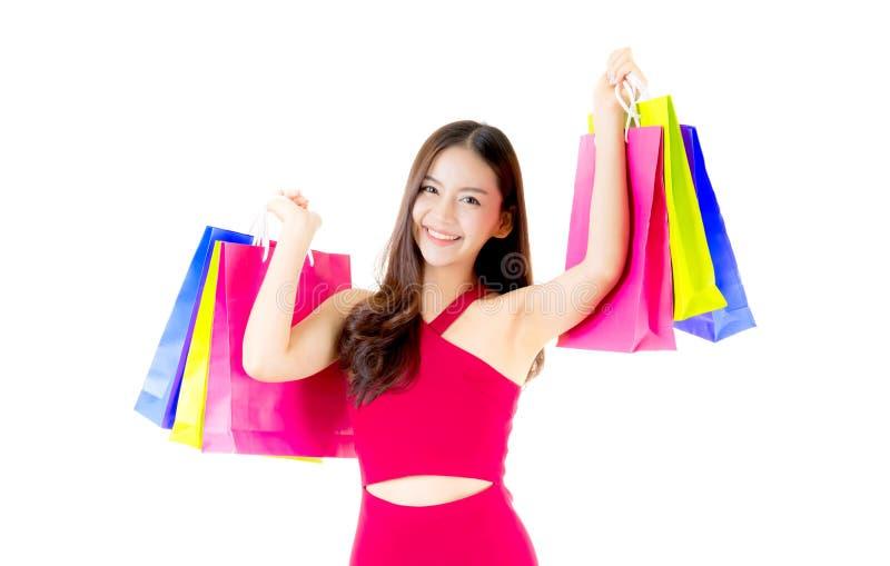 0portrait de uma mulher asiática entusiasmado feliz na posição vermelha e no saco de compras do vestido imagem de stock