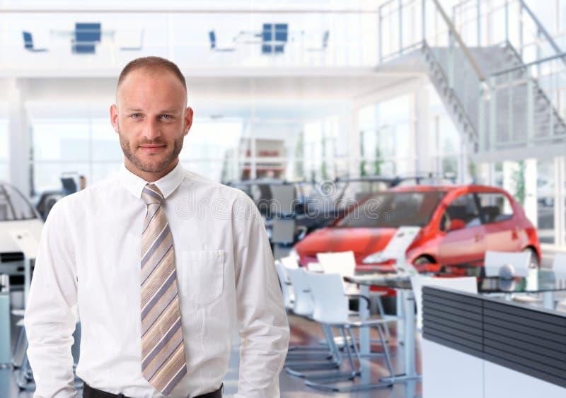 Portrait de vendeur de voiture dans la salle d'exposition image stock