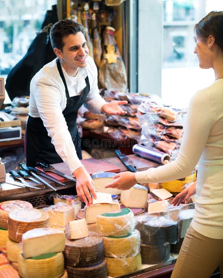 Portrait de vendeur offrant le fromage différent photos stock