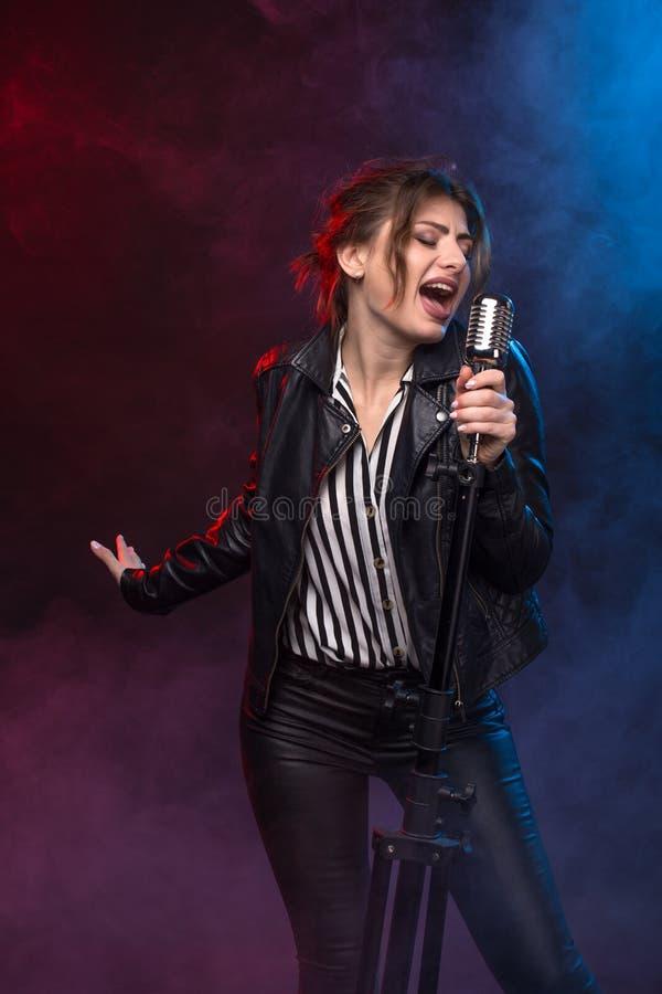 Portrait de veste en cuir de port et de garder de chanteur Rock expressif le rétro microphone de style photographie stock