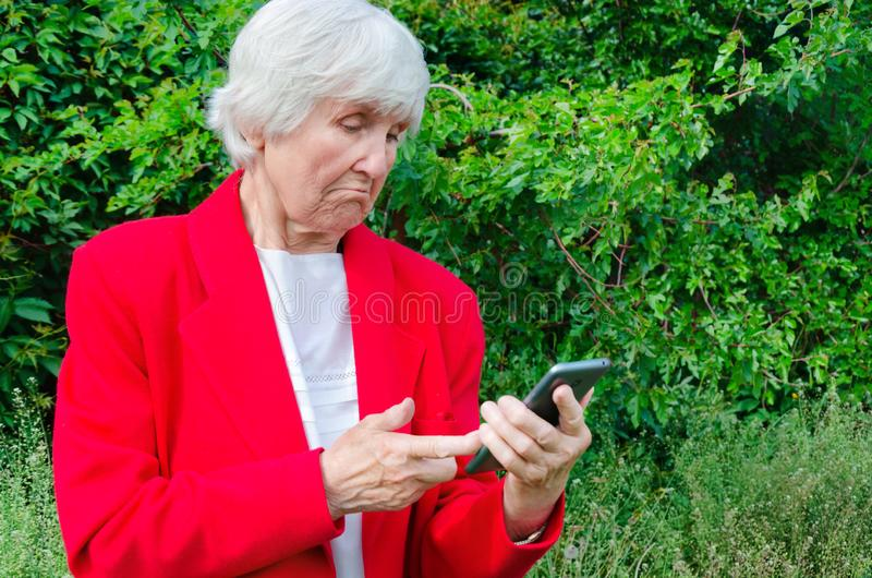 Portrait de vieil ext?rieur de technologie d'utilisation de grand-m?re au jour du soleil contact caucasien moderne de doigt de ma photographie stock