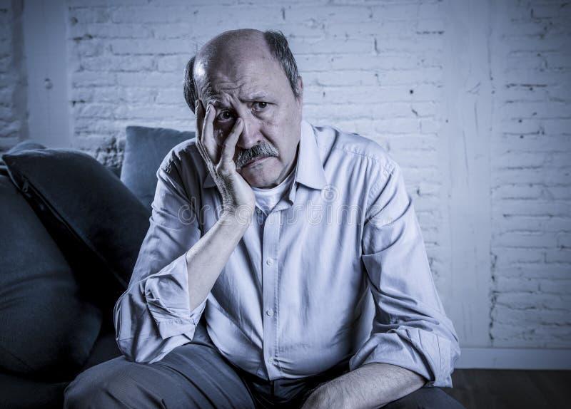 Portrait de vieil homme mûr supérieur sur son à la maison seul divan 60s photo stock