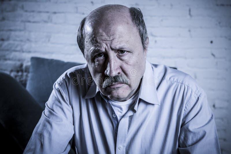 Portrait de vieil homme mûr supérieur sur son à la maison seul divan 60s images stock