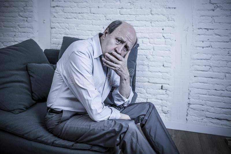 Portrait de vieil homme mûr supérieur sur son à la maison seul divan 60s image libre de droits