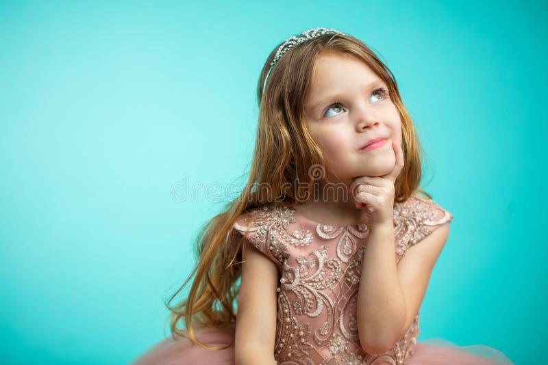 Portrait de vieille fille de quatre ans adorable dans la robe rose de princesse d'isolement au-dessus du bleu images libres de droits