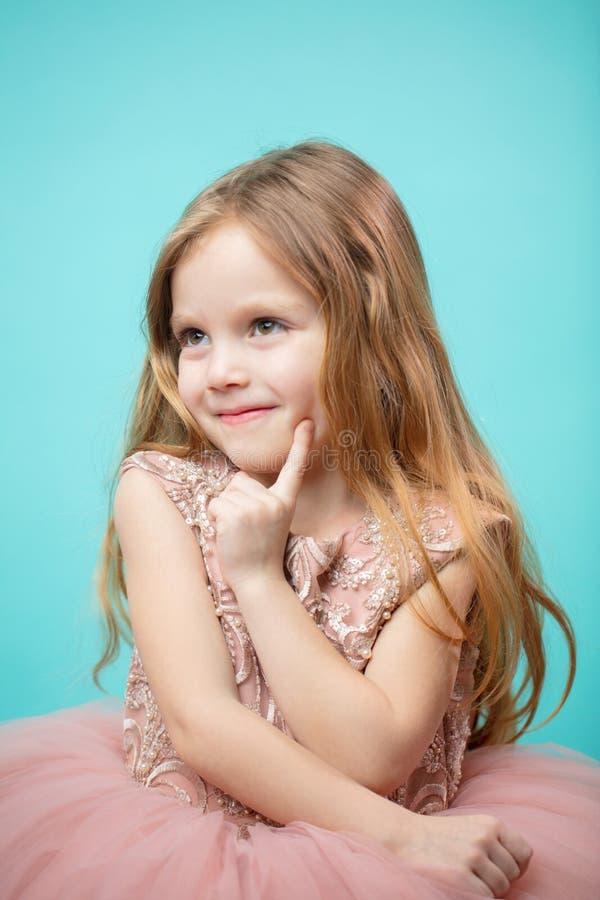 Portrait de vieille fille de quatre ans adorable dans la robe rose de princesse d'isolement au-dessus du bleu image libre de droits