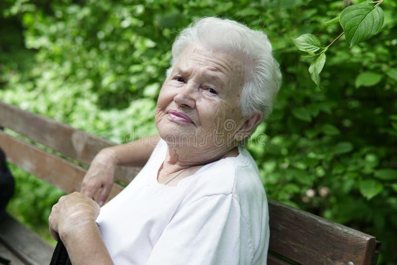 Portrait de vieille mamie sur un banc de parc gentil photographie stock
