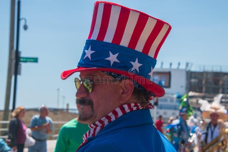 Portrait de vue de côté d'un homme utilisant un chapeau supérieur blanc de drapeau et bleu rouge américain et une veste bleue photos stock