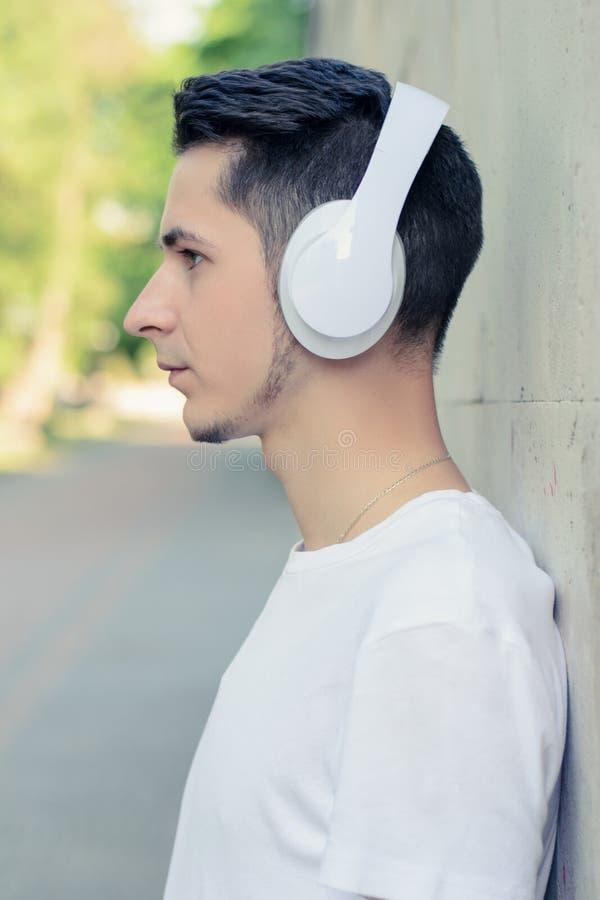 Portrait de vue de côté du jeune type beau se penchant sur le mur et appréciant sa musique préférée utilisant de grands écouteurs images libres de droits
