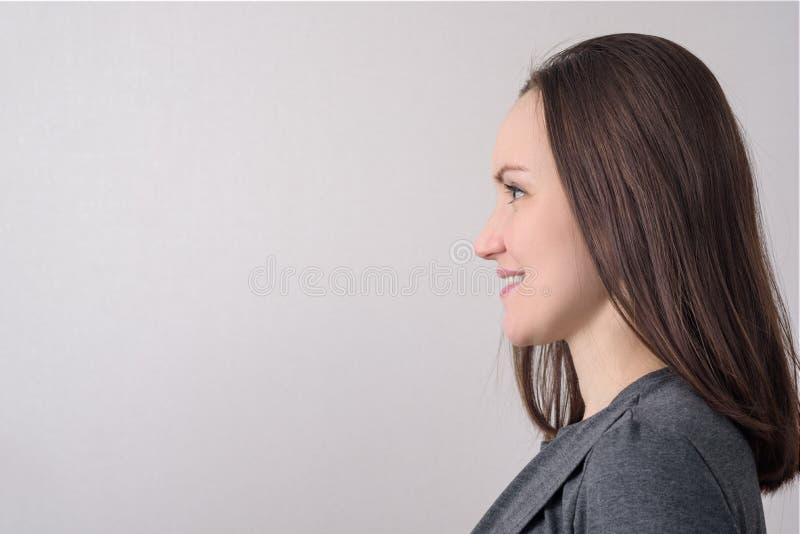 Portrait de vue de côté de femme caucasienne sur le fond clair photos stock