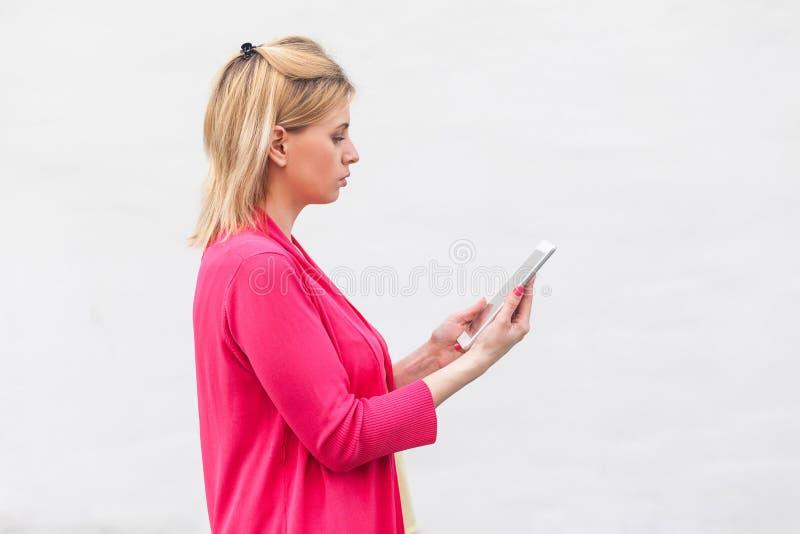 Portrait de vue de côté de jeune femme réfléchie de femme d'affaires dans la position rose de chemisier, utilisant le comprimé à  photos stock