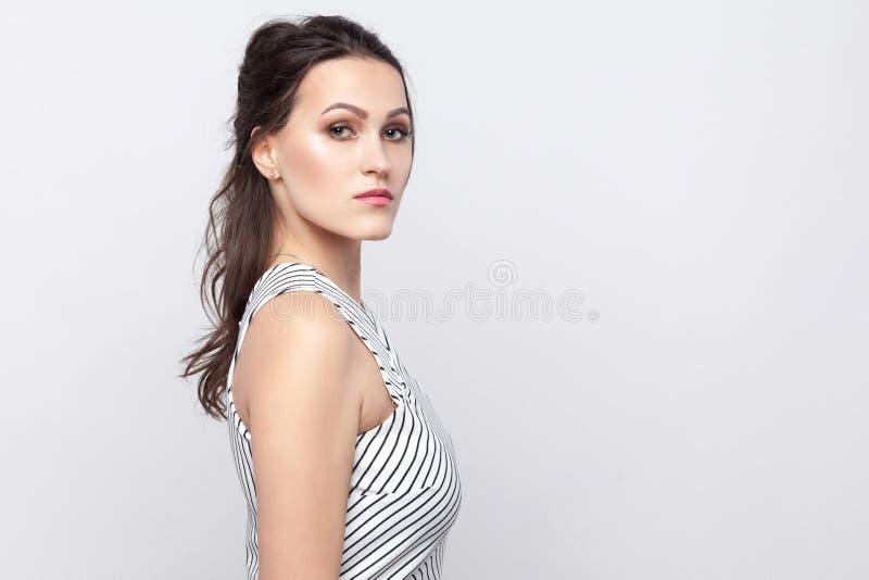 Portrait de vue de côté de profil de belle jeune femme sérieuse de brune avec le maquillage et la position rayée de robe et regar photos stock