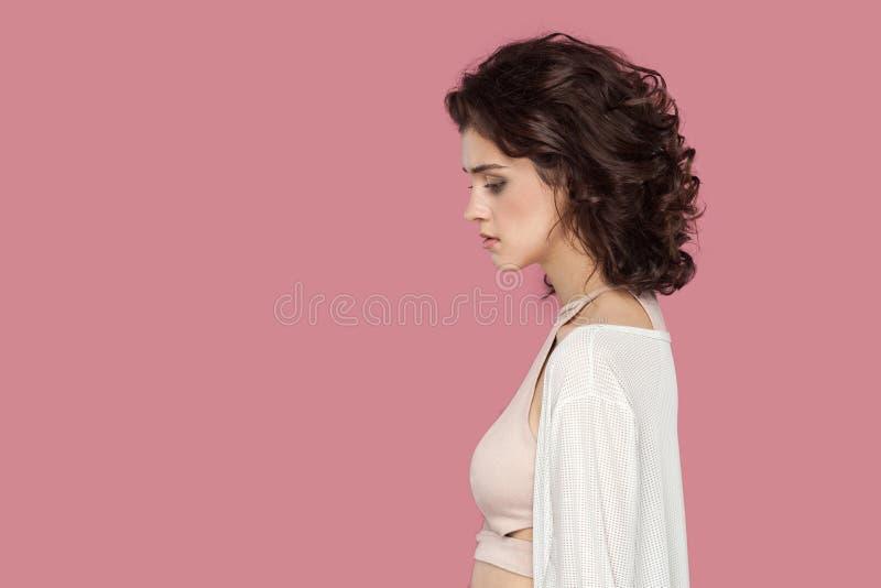 Portrait de vue de c?t? de profil de belle jeune femme triste de brune avec la coiffure boucl?e dans la position de style occasio photo stock